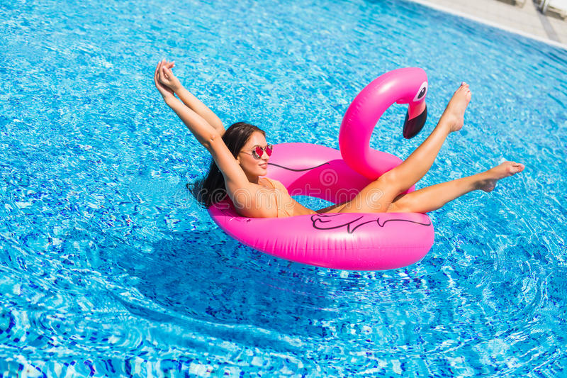 Beautiful woman, wearing swimsuit, lying on a pink flamingo air mattress in a pool of blue water, summer stock photography