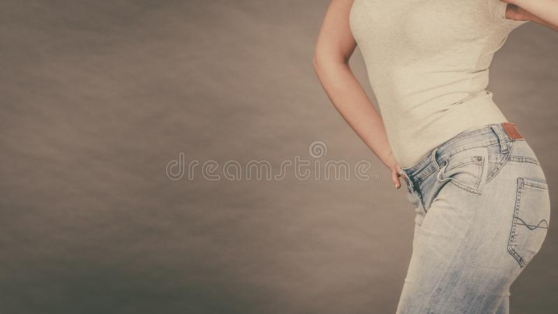 Woman wearing tight slim jeans and white tshirt stock image