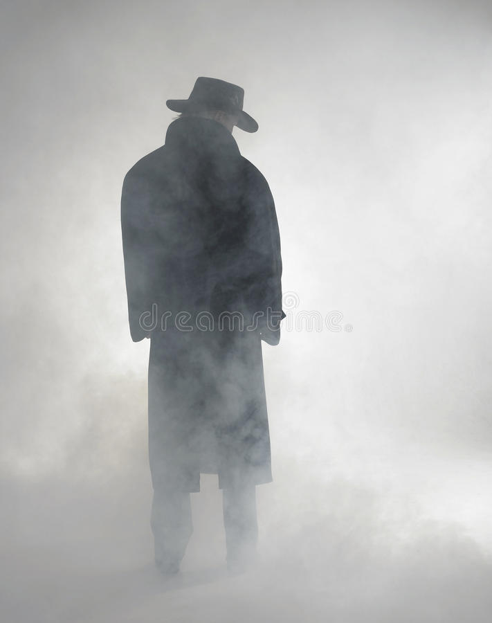 Woman wearing trench coat and standing in fog. Woman with dark coat standing in the fog royalty free stock photos
