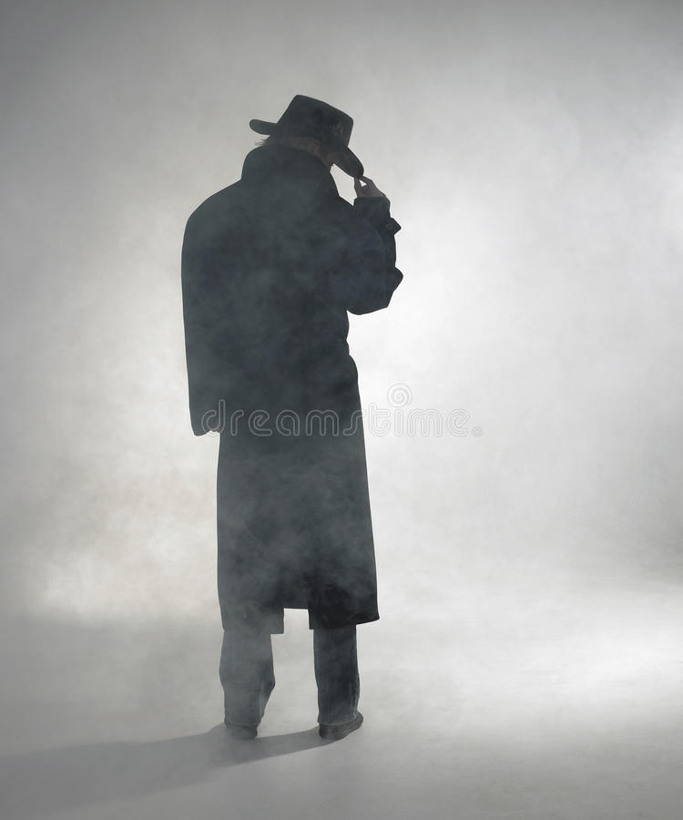 Woman wearing trench coat and standing in fog. Woman with dark coat standing in the fog royalty free stock image