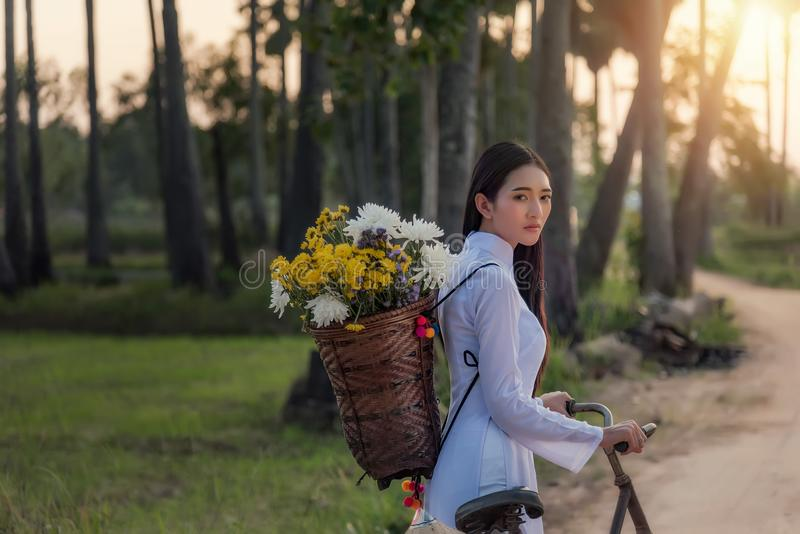 Woman wearing a Vietnamese dress Ao Dai are ride on a bicycle royalty free stock photos