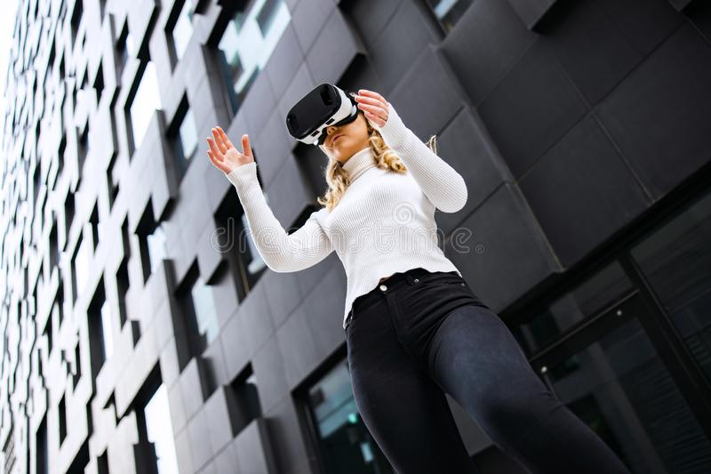 Woman Wearing Virtual Reality Glasses In City stock photo