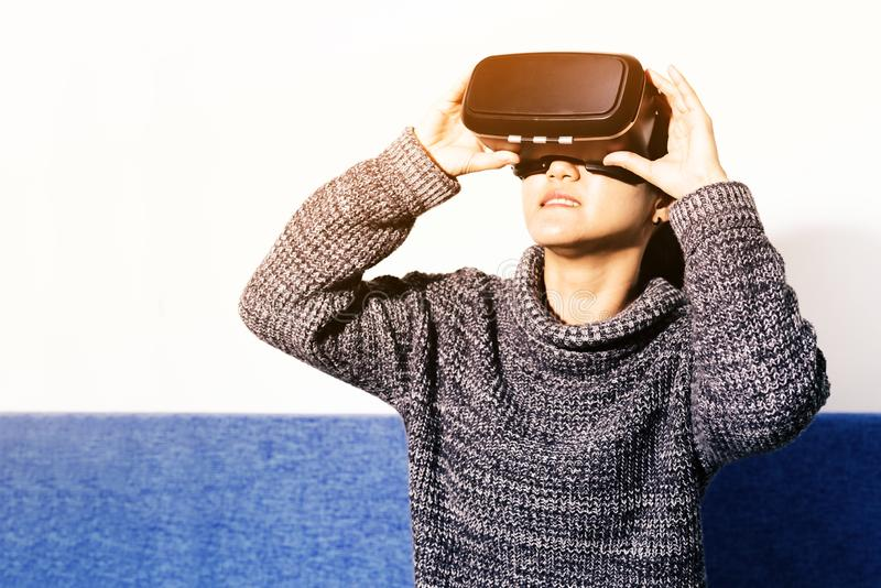 Woman wearing virtual reality glasses. Smartphone using with VR headset royalty free stock image