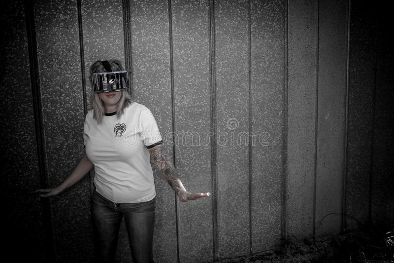 Woman Wearing Virtual Reality Headset Standing Beside Wall stock photography