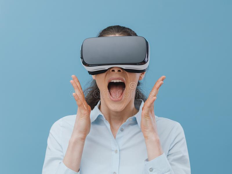 Woman experiencing virtual reality. Woman wearing a VR headset and experiencing virtual reality, she is amazed and surprised royalty free stock photo