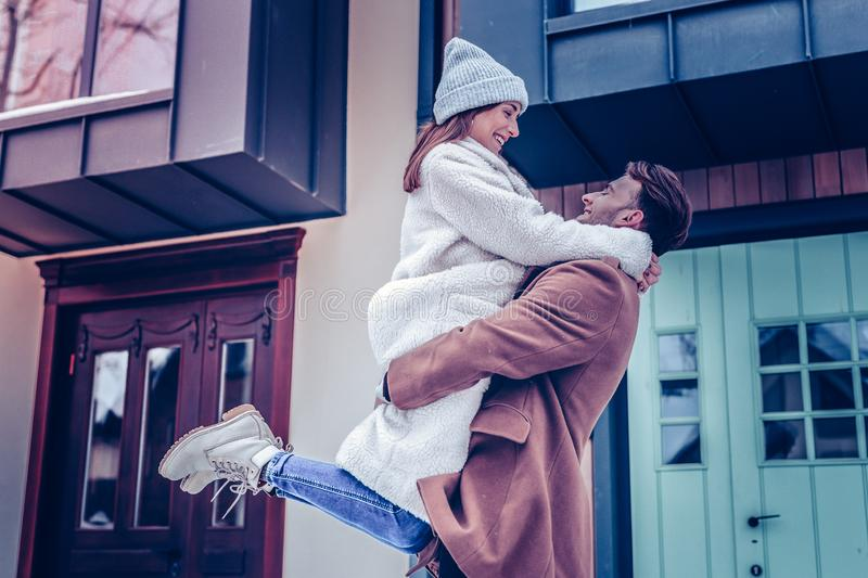Woman wearing warm beige coat jumping into hands of husband royalty free stock images