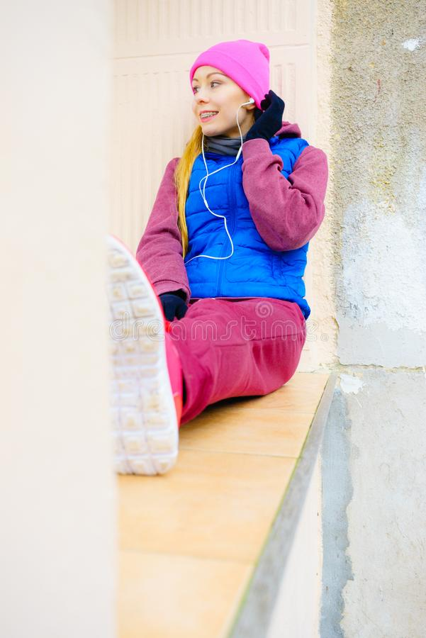 Woman wearing warm sportswear relaxing after exercising royalty free stock images