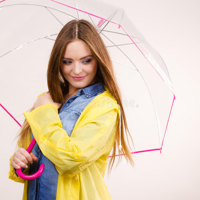 Woman wearing waterproof coat under umbrella. Woman rainy smiling girl wearing waterproof yellow coat standing under umbrella having fun. Meteorology stock photos