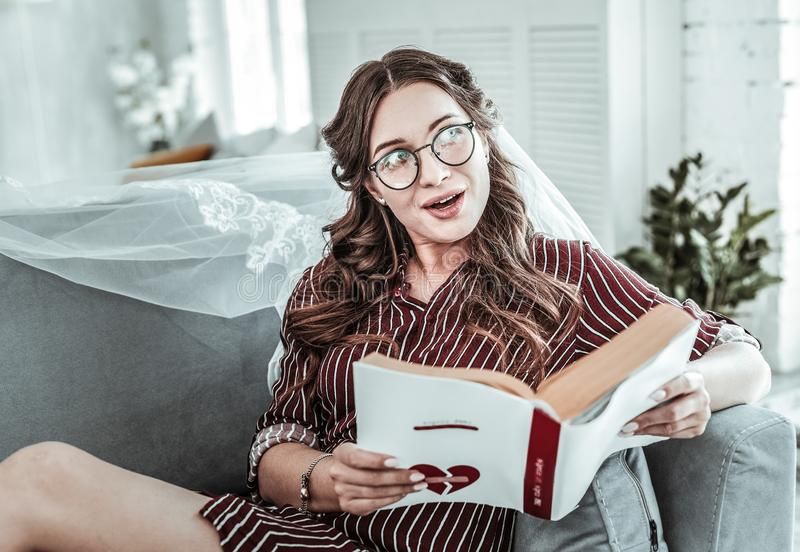 Woman wearing wedding vail reading a book stock image