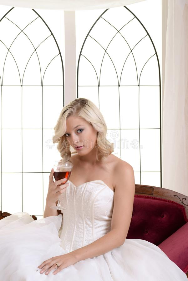 Woman wearing white ball dress holding glass red wine royalty free stock photography