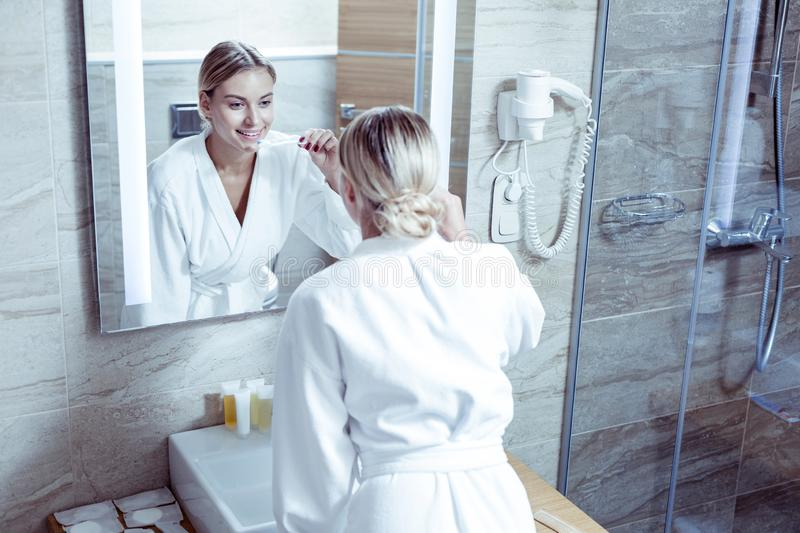 Woman wearing white bathrobe brushing teeth before going to bed royalty free stock photography