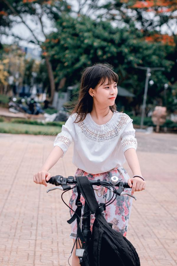 Woman Wearing White Blouse Riding Bicycle on Brown Concrete Tiled Area Near Trees stock image