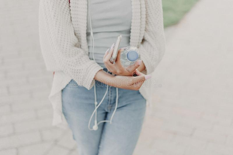 Woman Wearing White Cardigan Holding Plastic Bottle royalty free stock photo
