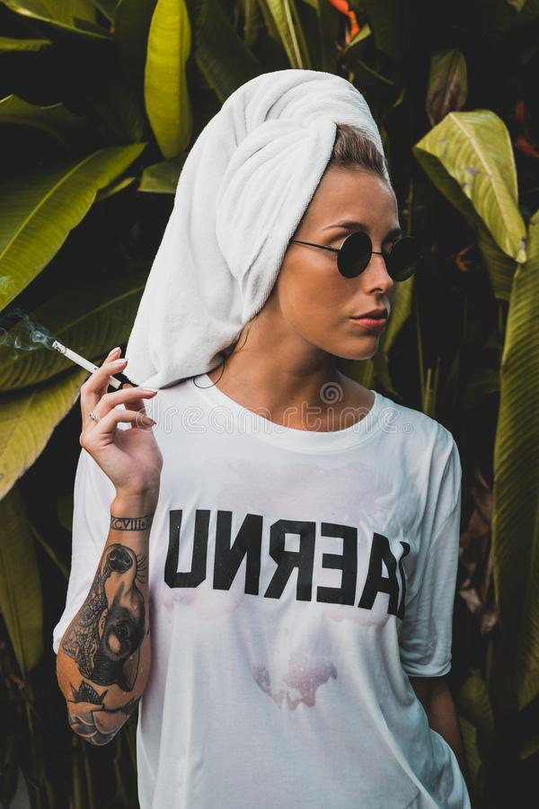 Woman Wearing White Crew-neck Shirt and Black Framed Sunglasses With White Bath Towel on Her Head Holding Cigarette Stick royalty free stock photography