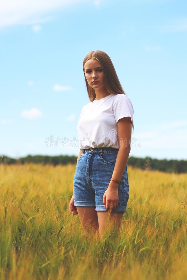 Woman Wearing White Crew-neck T-shirt, Blue Denim Cuff Short Shorts While Standing on Grass Field stock photos