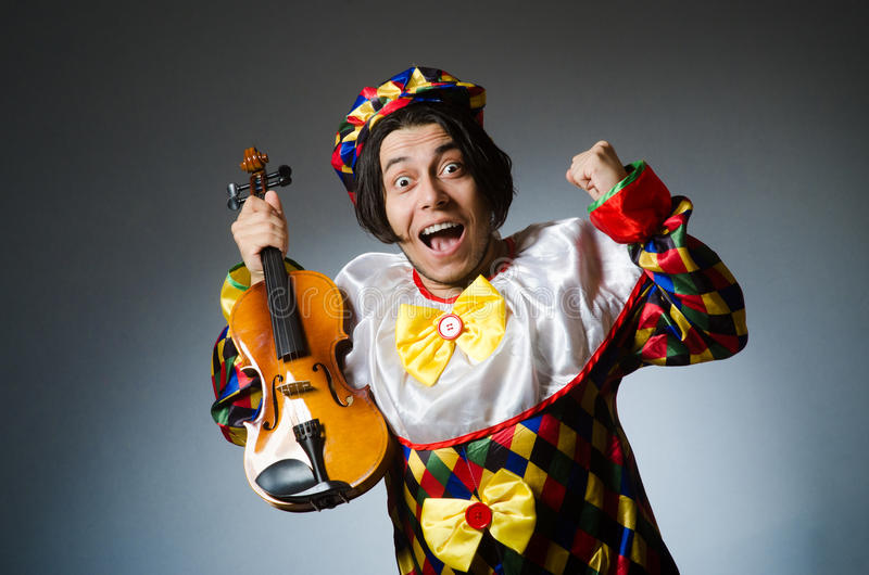 The woman wearing white dress isolated on white. Funny violin clown player in musical concept royalty free stock image