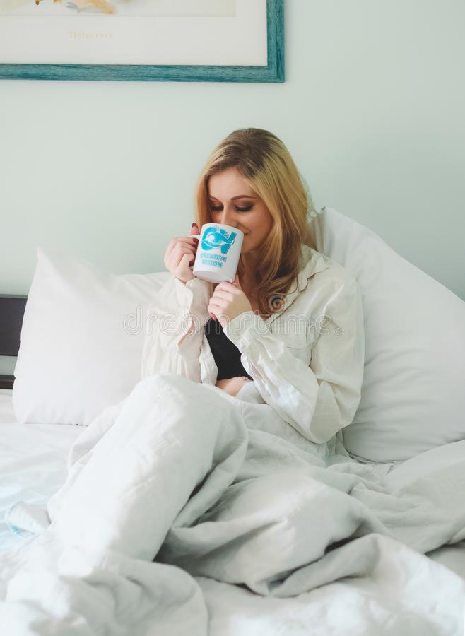 Woman Wearing White Dress Shirt Sitting on Bed While Drinking Through White Ceramic Mug royalty free stock photography
