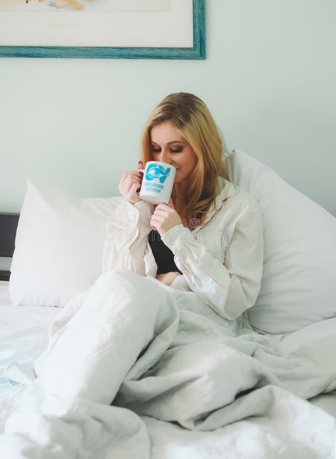 Woman Wearing White Dress Shirt Sitting on Bed While Drinking Through White Ceramic Mug royalty free stock photography