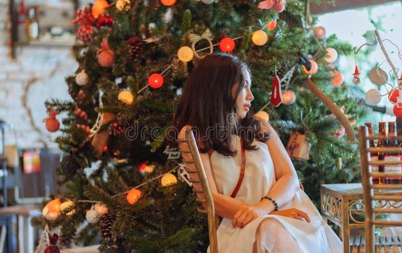 Woman Wearing White Dress Sitting Near Christmas Tree stock photography