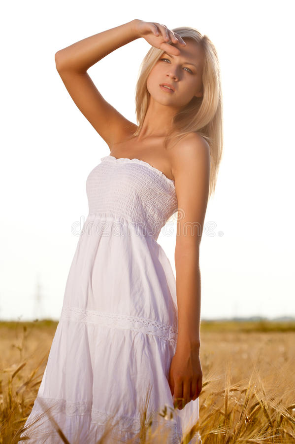 Woman wearing white dress on wheat field stock photography