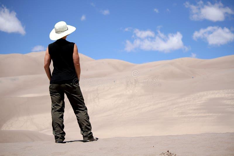 Woman standing in desert sand dunes. stock photos