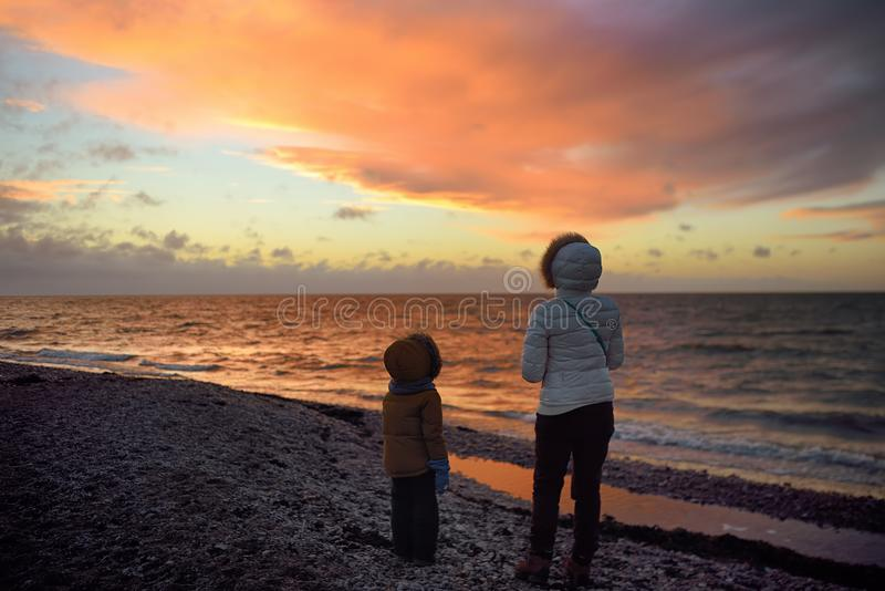 Woman wearing white jacket and little child are walking on Baltic Sea coast on sunset of winter day. Outdoors activity for family. With kids in winter. Estonia stock photos