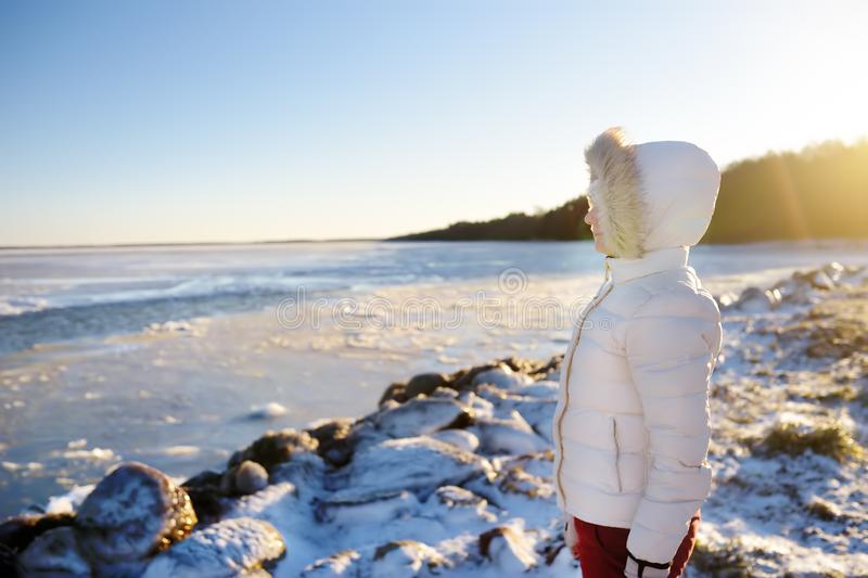 Woman wearing white jacket is walking on iced Baltic Sea coast in sunny winter day royalty free stock photos