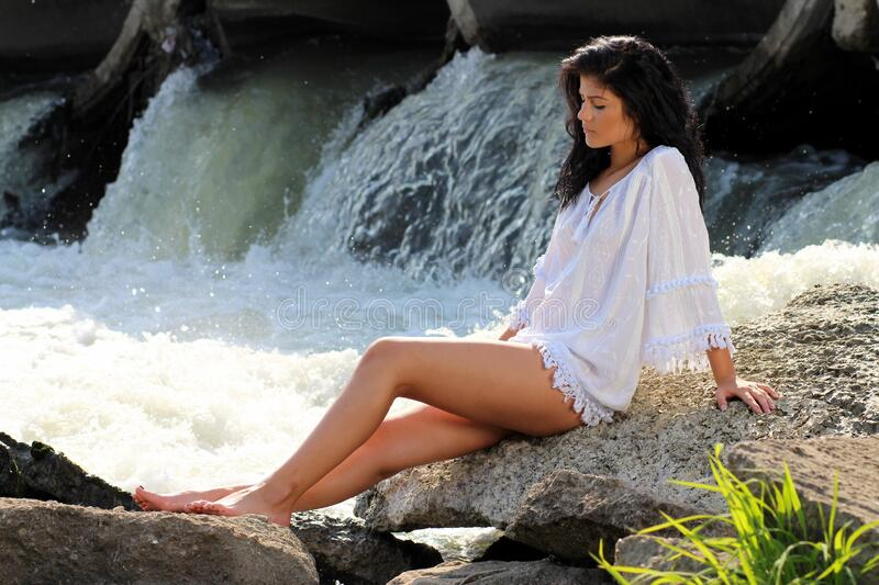 Woman Wearing White Long Sleeved Dress Sitting on a Rock Beside Flowing Body of Water during Daytime royalty free stock images