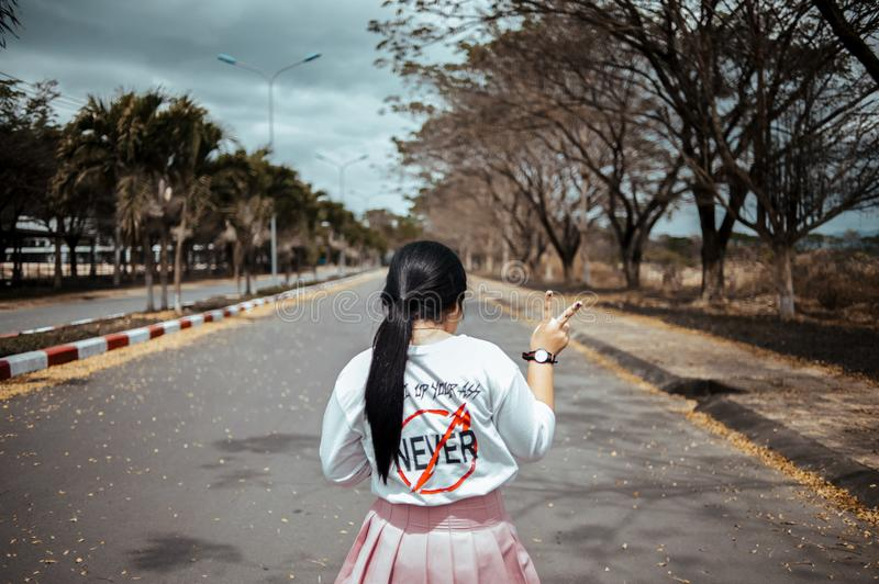 Woman Wearing White Long-sleeved Shirt and Pink Pleated Skirt Standing on Asphalt Road Between Green Trees Under Gray Sky at Dayti stock photography