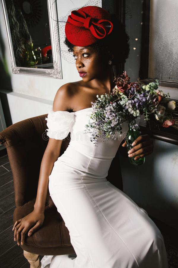 Woman Wearing White Off-shoulder Bodycon Dress Holding Flower Arrangement in Vase royalty free stock photo