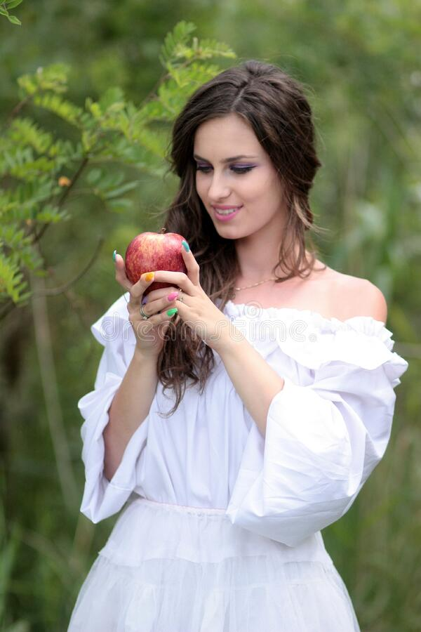 Woman Wearing White Off Shoulder Top Holding Red Apple Fruit stock photography