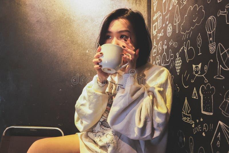 Woman Wearing White over Shirt Holding White Ceramic Mug Beside Black Printed Wall stock image