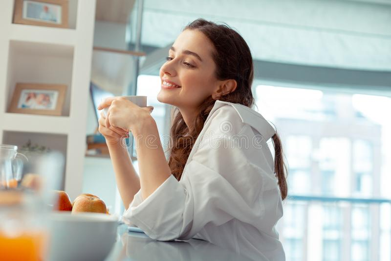 Woman wearing white shirt feeling relaxed drinking coffee stock photo