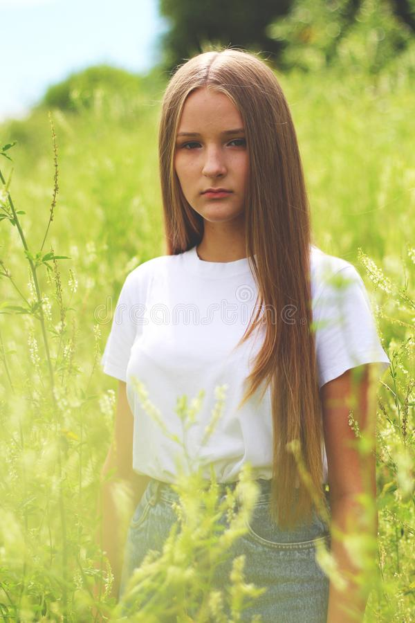 Woman Wearing White Shirt and Gray Denim Bottoms on Green Grass Field royalty free stock image