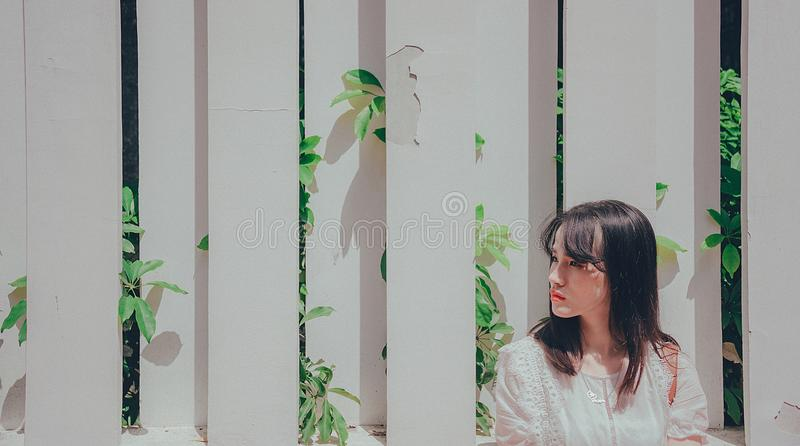 Woman Wearing White Shirt Leaning on White Wooden Fence With Plants stock photography