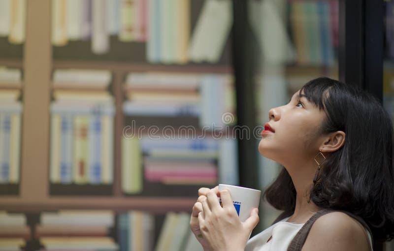 Woman Wearing White Shirt Looking on Top Holding White Ceramic Mug stock image