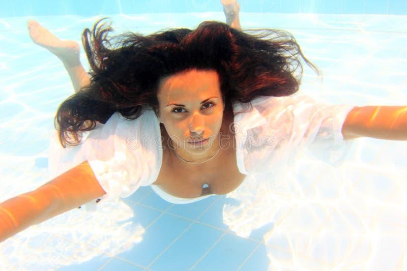 Young woman underwater, wearing thin white shirt Stock