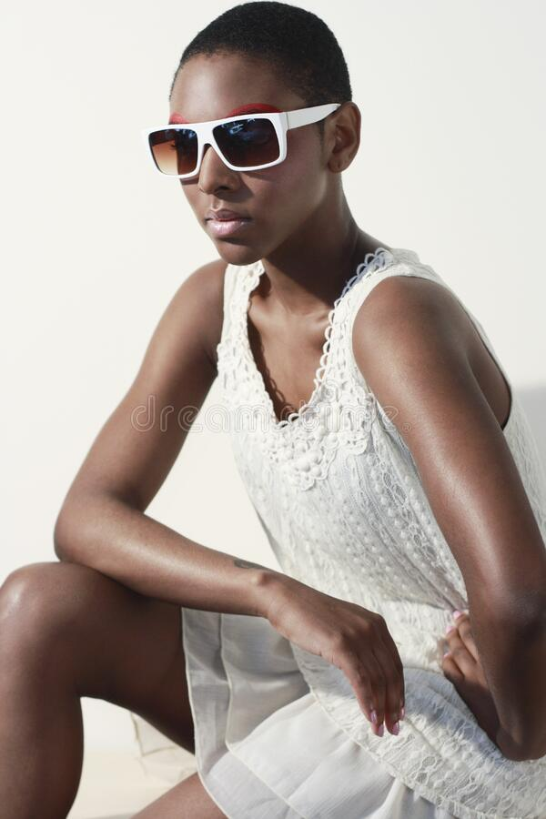 Woman Wearing White Tank Dress and White Frame Sunglasses Sitting and Making a Pose stock images