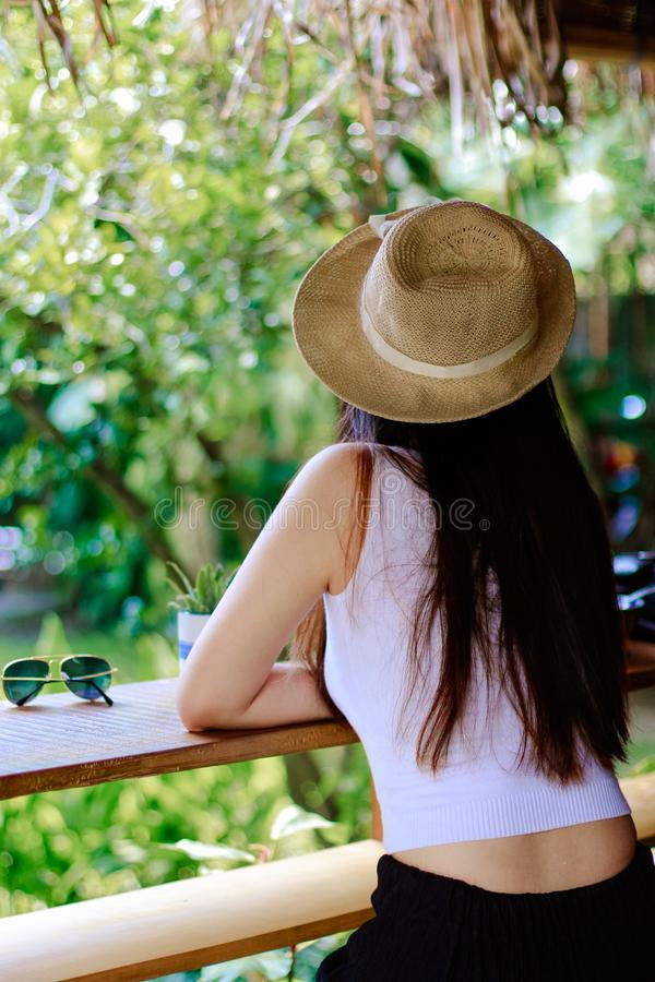 Woman Wearing White Tank Top and Black Pants With Brown Sun Hat royalty free stock photo