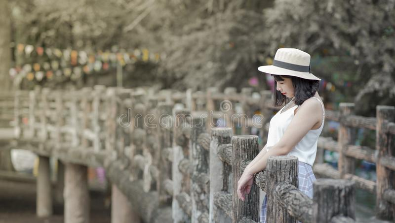 Woman Wearing White Tank Top and White Hat Standing on a Boardwalk stock images