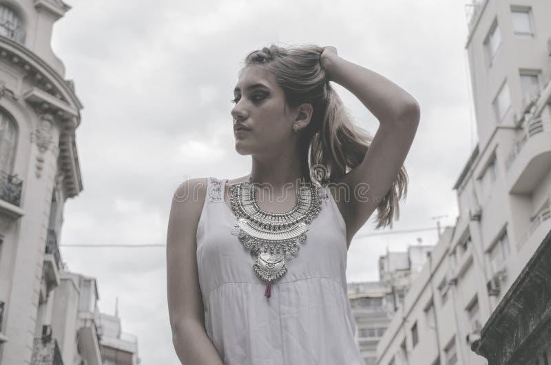 Woman Wearing White Tank Top Holding Hair Pose stock photos