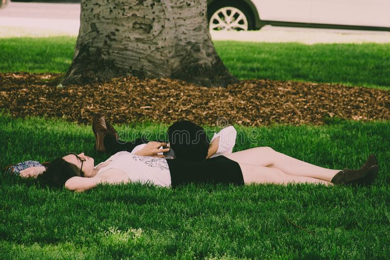 Woman Wearing White Tank Top Lying On Green Grass stock photos