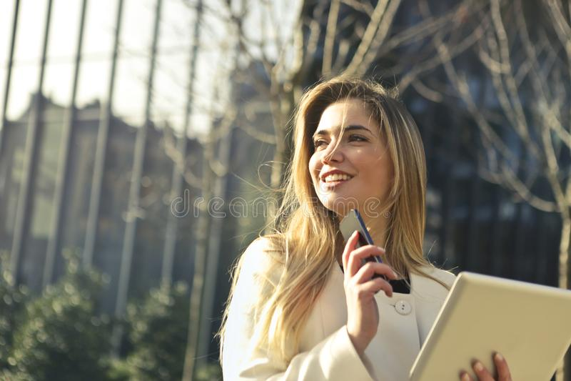 Woman Wearing White Top Holding Smartphone and Tablet stock photo