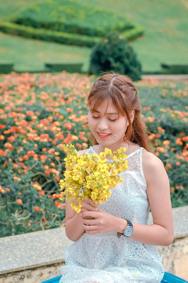 Woman Wearing White Top Holding Yellow Petaled Flowers stock image