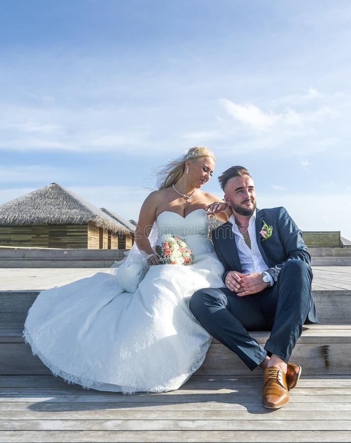 Woman Wearing White Wedding Gown Sitting Near Man Wearing Black Suit Jacket and Pants royalty free stock images