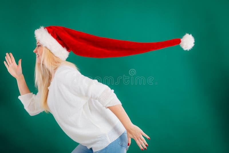 Woman wearing windblown santa hat royalty free stock photo
