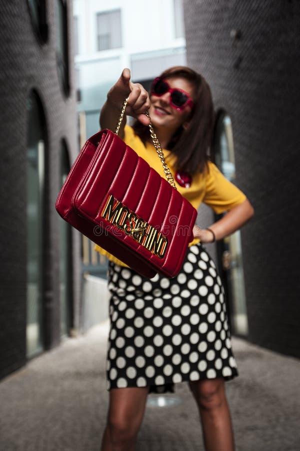 Woman Wearing Yellow Crew-neck T-shirt While Holding Red Handbag royalty free stock image