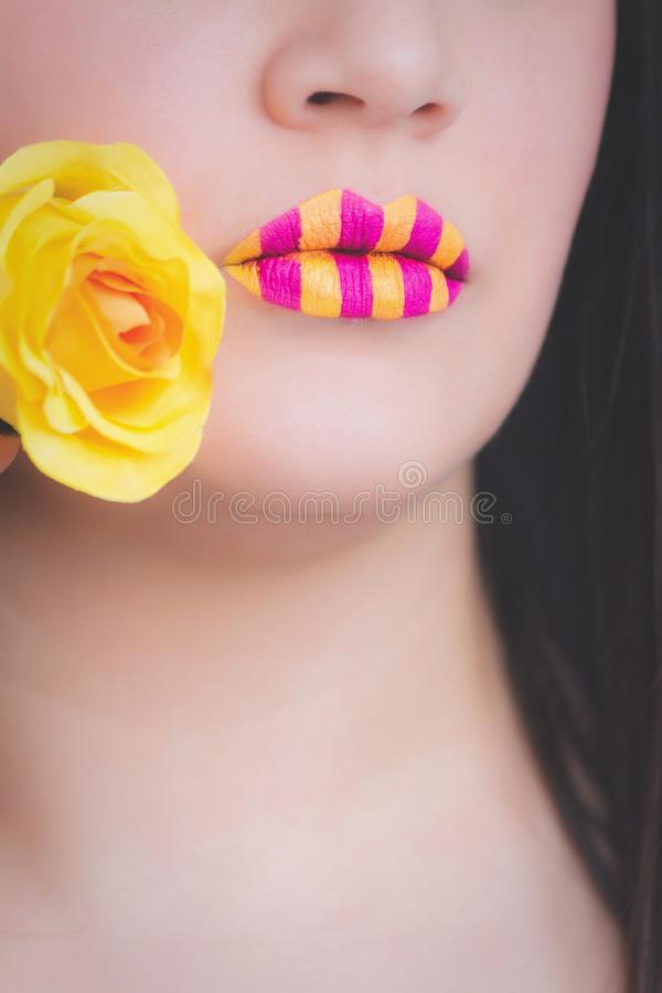 Woman Wearing Yellow and Pink Striped Lipstick Holding Yellow Rose stock photos