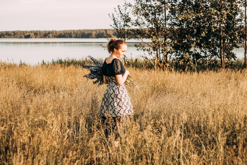 Woman Wears Black and Grey Dress Stands in Field stock images