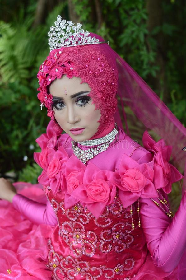 Woman Wears Pink Long-sleeved Dress With Crown stock images